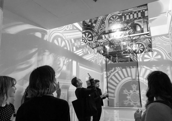 Black and white photo of people looking at intricate shadows on a wall