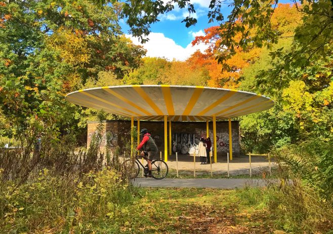 Cyclist riding past the Oculus, a concrete UFO shaped structure