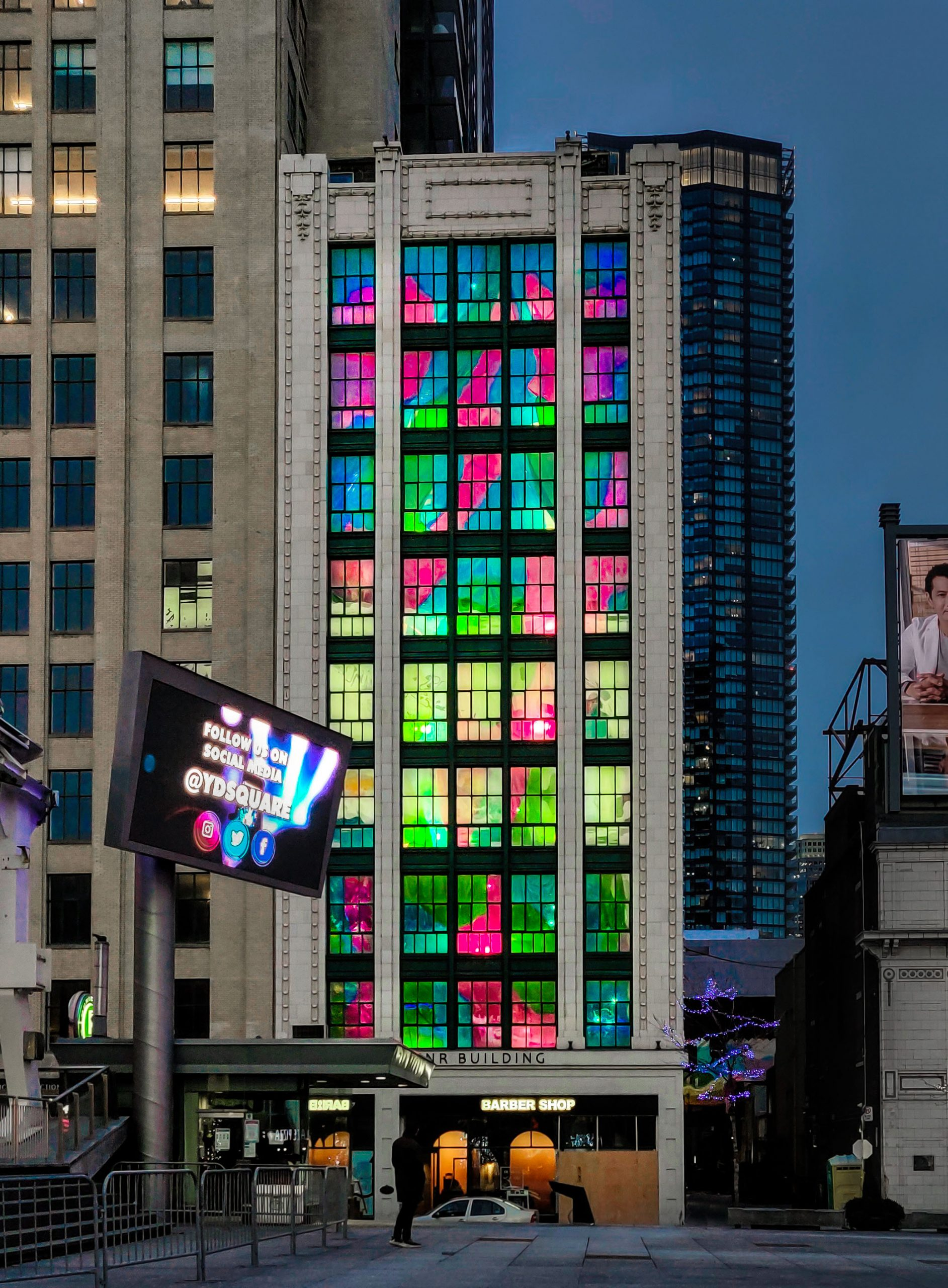 Grey concrete highrise with colorful window panes