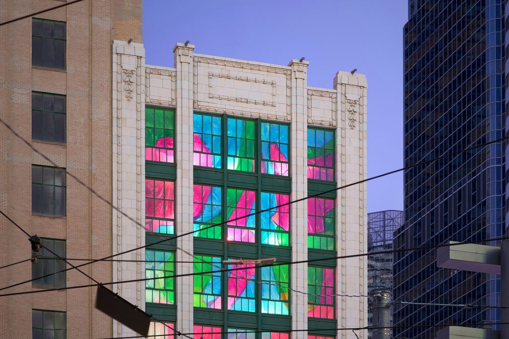 Close up photo of top 3 storeys of 19 Dundas Square with colourful abstract window installation.