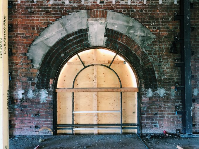 Arched window frame boarded in plywood