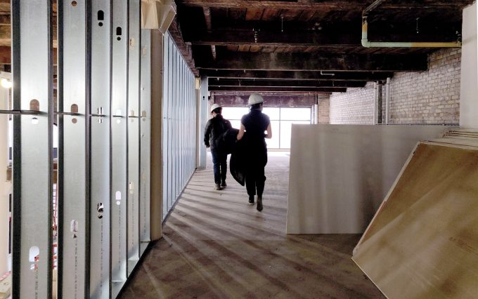 Two people waking through building under renovation