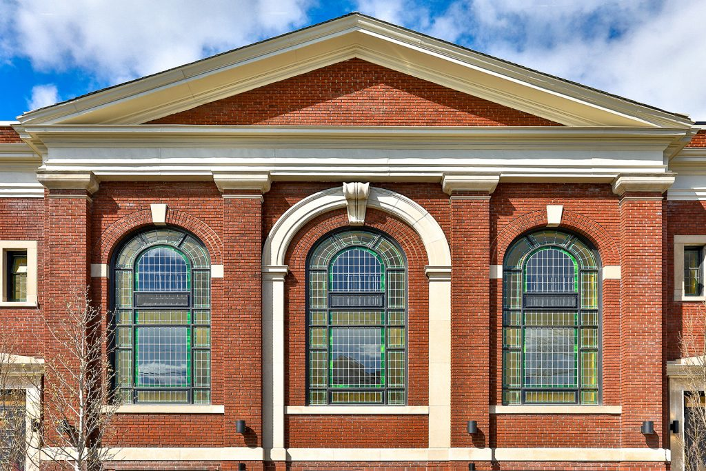 Brick temple church facade restored with three arched stained glass windows.