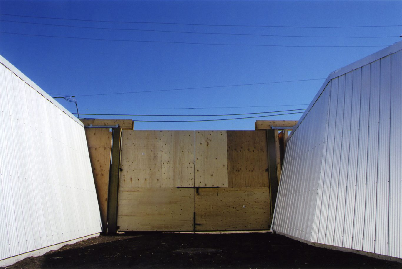 Two corrugated white shed walls against a plywood gate